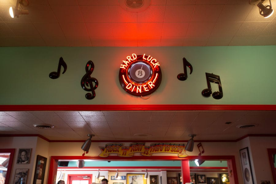 """neon sign that reads """"Hard Luck Diner"""" displayed on wall in Mel's"""